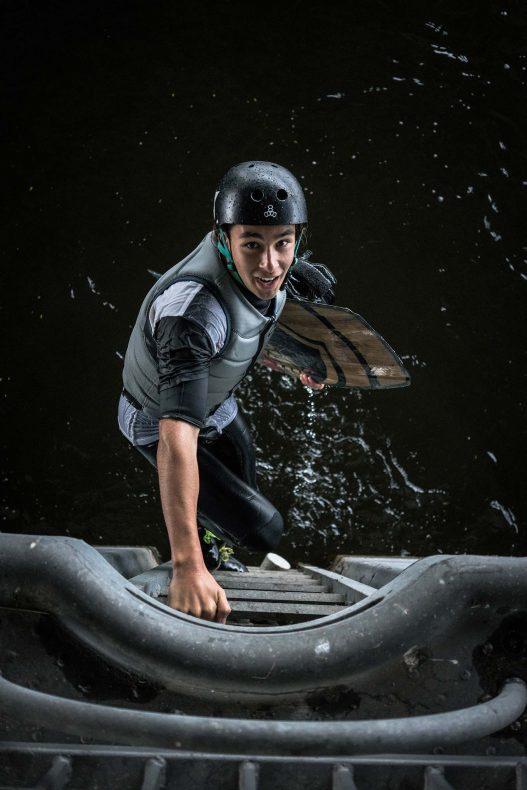 Wakeboarder steigt Leiter ins Wasser herab