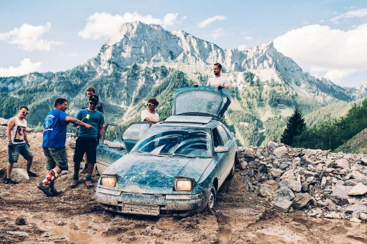 Gruppe von stehenden Männern um ein Auto in den Bergen