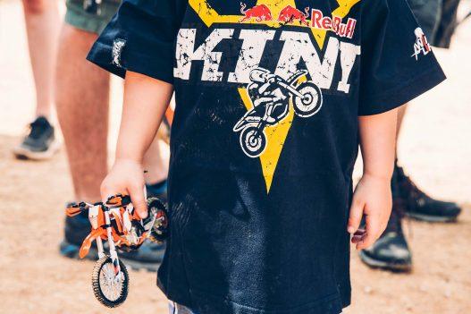 Kind mit Red Bull Tshirt und Bike in der Hand