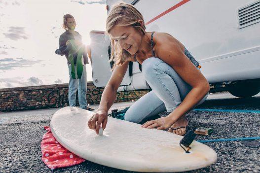 Blonde Surferin beim Waxen ihres weißen Surfboards