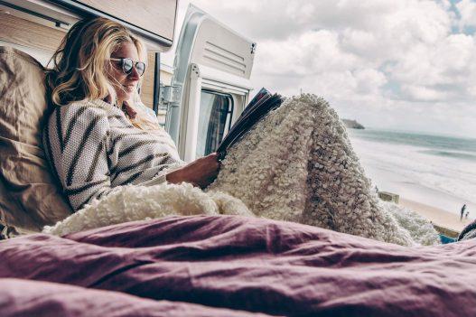 Frau chillt in Sunlight Van und ist mit einer Decke zugedeckt