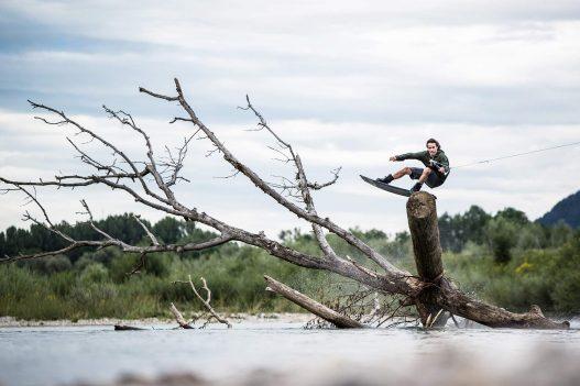 Wakeboarder springt über Baumstamm im Wasser