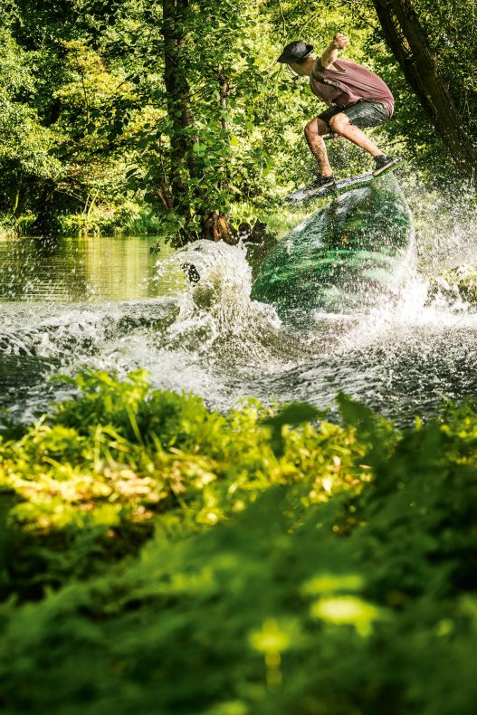 Wakeboarder in Action auf See im Wald