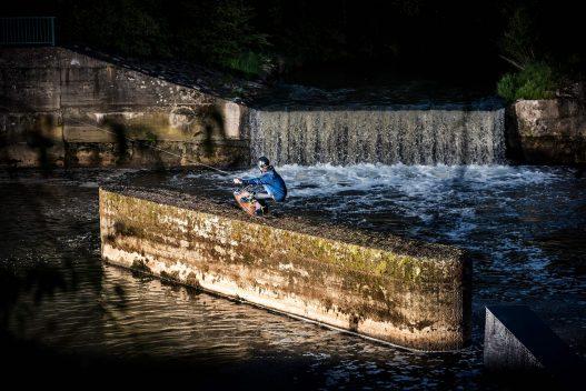 Wakeboarder springt über Damm