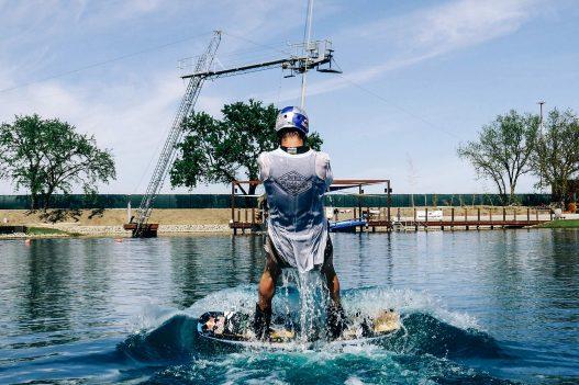 Wakeboarder mit Helm am Board im Wasser